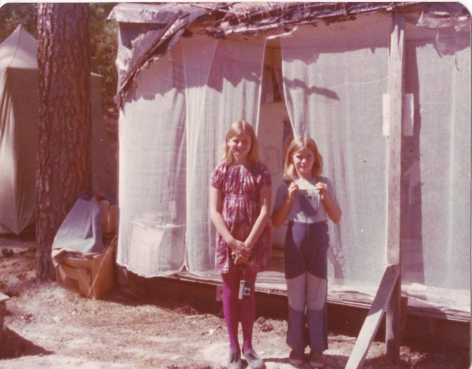 In 1976 my mom moved my sister and me out of San Diego and brought us to the Sierra Nevada foothills. Her plan had been to live in Ananda, a religious group led by an American who went by the name Swami Kriananda. She didn't know until we got there that it cost $1000 to join as a member of the community. So she found an old Bureau of Land Management road that led to a trashed trailer that only had three walls. She cleaned it up, added some cheese cloth to make a fourth wall, and we used the space until the weather changed with the season. We had to be sly when we went down the road because we were squatting on government land. The photo shows me with my sister. You can see the tent where we slept in the background. (Private photo from Barbara's own collection. All rights reserved.)